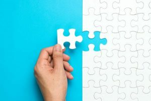 An image of an all white puzzle on a blue surface, while a hand is about to add the final piece.