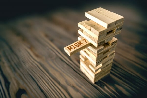 "An image for risk management, showing a jenga tower with one wooden block highlighting the word ""risk"""