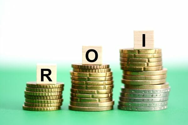 An image to symbolise return of investment. Three stacks of coins are arranged from small to large, with a block with a letter on top of each one, spelling R, O, I