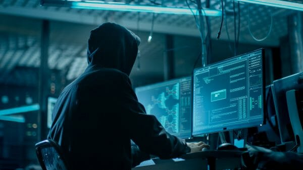 An image shot from the back of a darkened room to a hooded hacker breaking into corporate data servers. The room has dark a atmosphere, with multiple displays and cables everywhere.