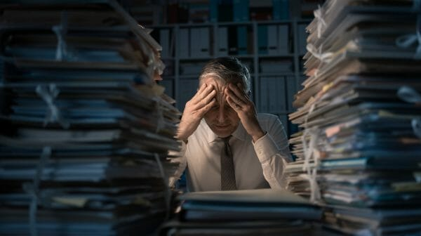 An image of a desperate businessman working late, flanked by tall piles of files and paperwork.