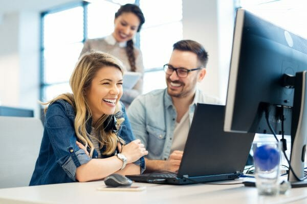 An image of business people and software developers working as a team and smiling in front of a computer