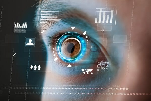 An image to demonstrate cyber technologies. Using a human eye, graphics are overlayed showing various icons and statistics.
