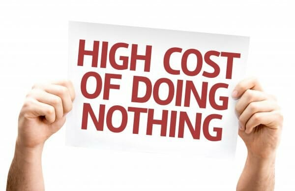 """An image of two hands holding a sign which reads """"High Cost Of Doing Nothing"""""""
